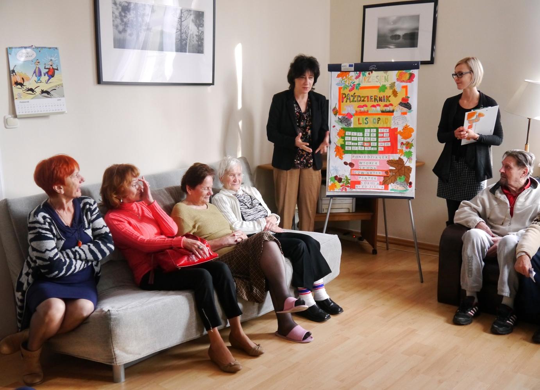 Wiceprezydent Sopotu stoi obok dużego stojącego kalendarza i mówi do siedzących na kanapie seniorów