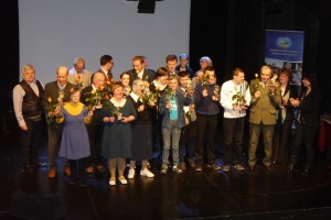 Aktorzy Teatru Ubogiego Relacji stoją na scenie trzymając w rękach róże i pozują do zdjęcia wspólnie z Panią Wiceprezydent Miasta Sopotu, Panią Dyrektor sopockiego MOPS-u oraz kierownikiem Ośrodka Adaptacyjnego