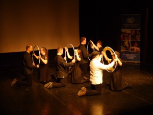Aktorzy znajdują się na scenie. W grupach dwusosobowych klęczą na przeciw siebie trzymając razem koło