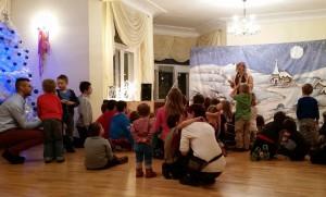 Grupa dzieci z opiekunami ogląda mężczyznę, który występuje na tle zimowego krajobrazu
