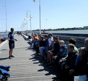 Grupa osob siedzi na przystani i słucha mężczyzny, który stoi przed nimi