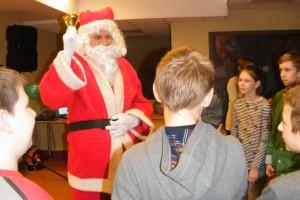 Mikołaj stoi wśród grupy dzieci i dzwoni dzwoneczkiem
