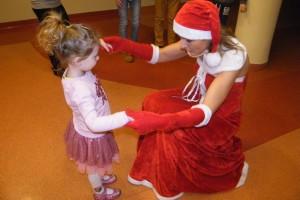 Dziewczyna przebrana za Mikołajkę kuca i trzyma za ręce dziewczynkę
