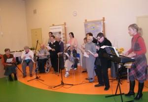 Grupa seniorów stoi, kilka osób siedzi na krzesłach i śpiewa trzymając w ręku kartki z tekstem. Po prawej stronie przy elektrycznym pianinie stoi pani, która na nim gra