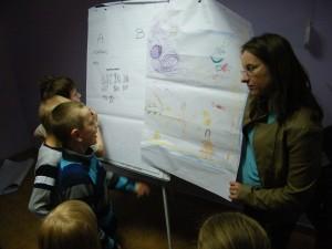 Pani psycholog pokazuje duży rysunek wykonany przez dzieci. Kilkoro dzieci stoi przed nią i opowiada o rysunku