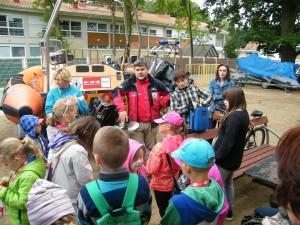 Grupa dzieci stoi wokół szefa sopockiego Wodnego Ochotniczego Pogotowia Ratunkowego