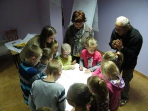 Gruopa dzieci z trojgiem dorosłych stoi wokół stołu i przygotowuje wsólny rysunek