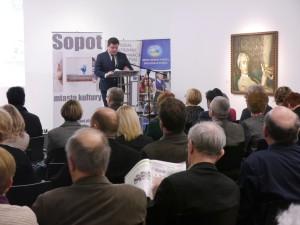 Pan Paweł Orłowski stoi przy pulpicie, naprzeci siedzącej grupy uczestników konferencji