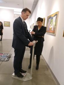 Jacek Rumiński stoi na wadze i trzyma się specjalnych uchwytów, przygląda się temu Pani Marzena Breza