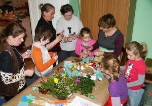 Grupa dzieci oraz pań stoi przy stole i przygotowuje świąteczne palmy i ozdoby