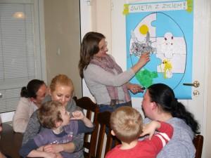 Mamy z dziećmi siedzą przy stole i patrzą na stojącą Panią psycholog, która układa na ścianie duże puzzle