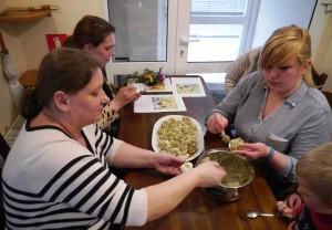 Trzy Panie siedzą przy stole i przygotowują faszerowane jajka