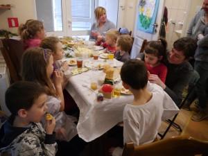 Grupa dzieci w towarzystwie mam siedzi przy stole i degustuje przygotowane potrawy