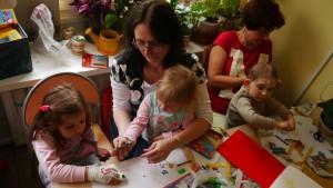 Dwie pracownice MOPS-u siedzą przy stole z trójką dzieci i rysują