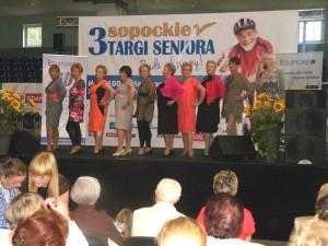 Pokaz mody na scenie - seniorki stoją ustawione bokiem i trzymają rękę na biodrze