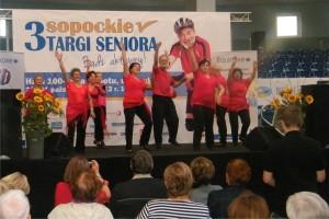 Grupa seniorów w czerwonych koszulkach i czarnych spodnaich tańczy na scenie, podnoszą ręce do góry
