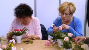 Dwie kobiety siedzą przy stole i układają w kubkach kwiaty