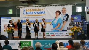 Cztery finalistki konkursu Miss po 50-te z przewieszonymi szarfami prezentują się na scenie