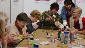 Grupa pań siedzi przy stole i maluje doniczki