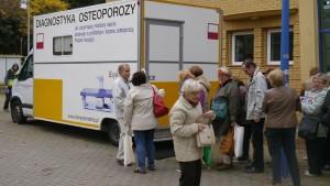 Grupa seniorów stoi przy samochodzie, w którym wykonuje się badanie gęstości kości