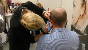 Kobieta pochyla się nad siedzącym mężczyzną i bada mu słuch specjalnym urządzeniem