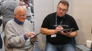 Dwaj mężczyźni siedzą, młodszy uczy starszego pana obsługi tabletu