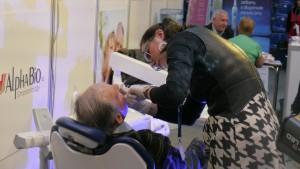 Pani stomatolog robi przegląd jamy ustnej mężczyzny, który siedzi na fotelu