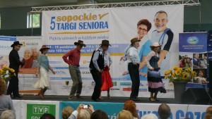 Grupa seniorów w kapeluszach tańczy na scenie taniec country
