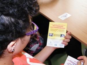 Dziewczyna siedzi w ławce szkolnej i czyta ulotkę, którą trzyma w ręku