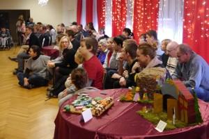 Grupa dzieci i młodzieży siedzi i słucha, na pierwszym planie stół, na którym znajdują się szopki