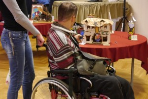 mężczyzna siedzi na wózku dla niepełnosprawnych i wobi telefonem komórkowym zdjęcie szopki ustawionej na stole
