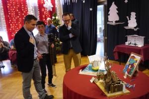 Wiceprezydent Sopotu Pan Marcin Skwierawski, Z-ca Dyrektora MOPSu Pan Andrzej Czekaj oraz Pani Małgorzata uczestniczka środowiskowego Domu Samopomocy w Sopocie stoją przy stole, na którym ustawione są szopki i rozmawiająiają szopki
