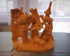 Szopka wykonana z gliny. Pan Jezus leży na tle sopockich kamienic oraz drzew