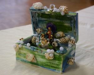 Szopka wykonana w szktatułce pomalowanej na morskie kolory z naklejownymi muszelkami oraz perłami