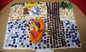 Szopka wykonana z guzików, które stanowią tło. Trzej królowie wykonani z modeliny płyną łódką do świętej rodziny