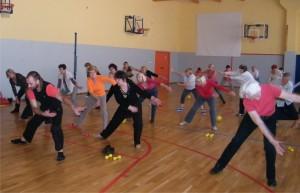 Grupa seniorów ćwiczy na sali gimnastycznej. Pochylają się i machają rękami do boku
