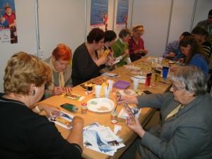 Grupa seniorek siedzi wokól stołu i maluje zakładki do książek