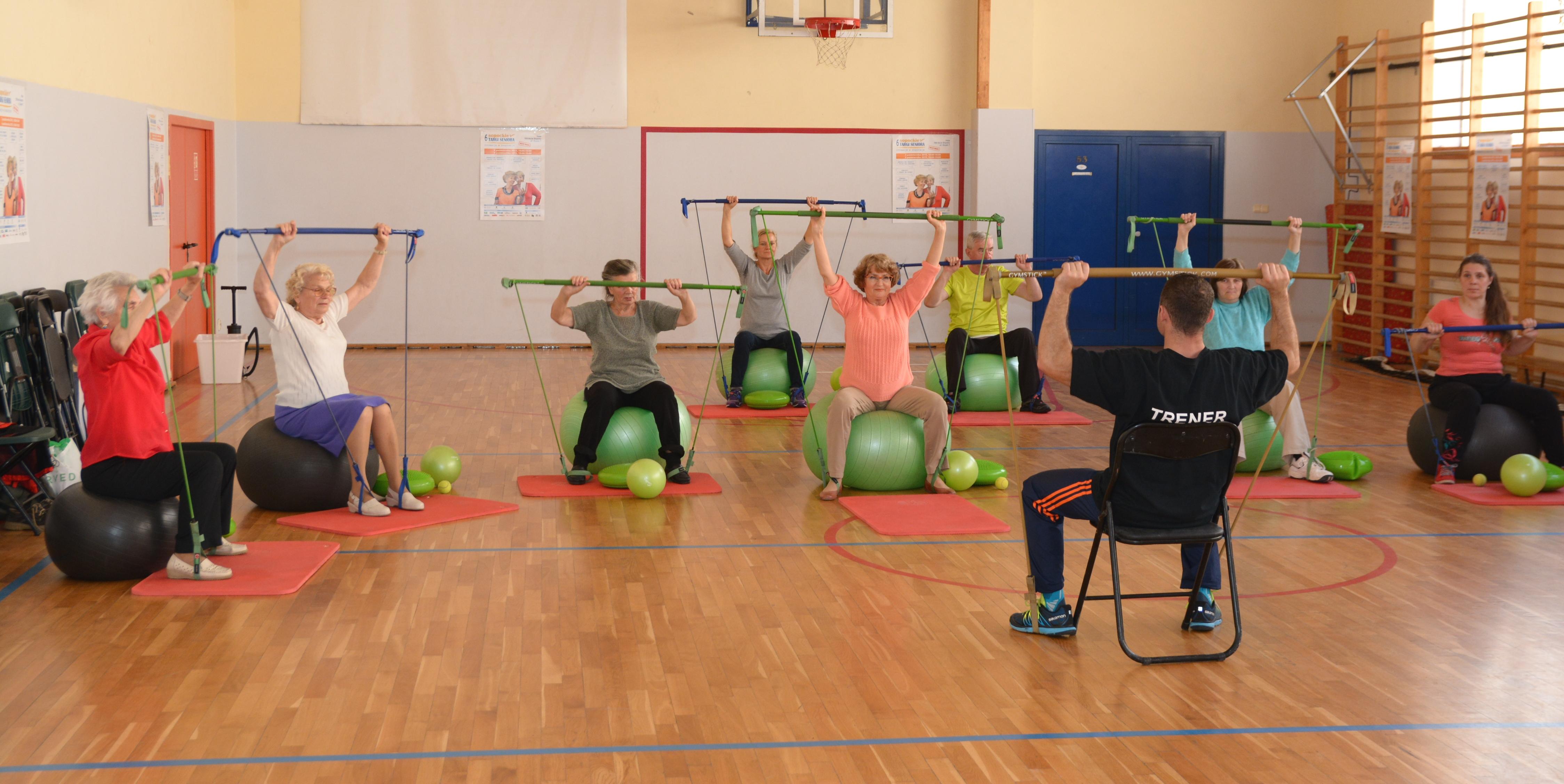 grupa seniorów siedzi na piłkach naprzeciw trenera i ćwiczy podnosząc do góry drążki