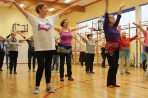 Grupa seniorek na sali gimnastycznej uczy się tańca, podnosi do góry ręce