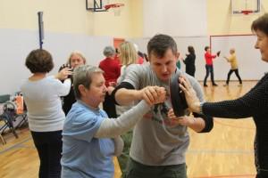 Grupa osób na sali gimnatycznej ćwiczy jak się obronić, jak uderzyć przeciwnika