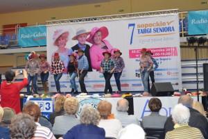 Grupa osób ubrana w kraciaste koszule oraz kapelusze tańczy na scenie