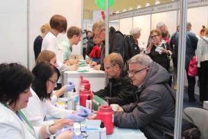 Na pierwszym planie dwóch panów siedzi naprzeciwko pielęgniarek, które wykonują badanie krwi z palca ręki