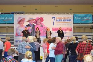 Grupa seniorów tańczy w parach pod sceną, na której stoją i śpiewają 4 osoby