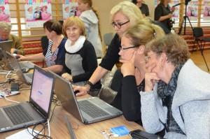 Grupa osób siedzi przy laptopach i uczy się obsługi komputera