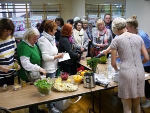 Grupa osób stoi przy stołach, na których znajdują się warzywa i owoce i obserwuje jak Pani dietetyk miksuje koktajl