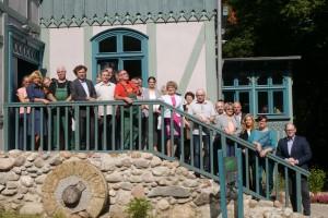 Grupa osób stoi na schodach na tle budynku