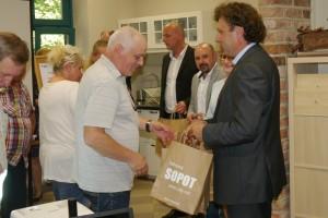 Na pierwszym planie Prezydent Sopotu wręcza papierową torebkę z napisem Sopot mężczyźnie