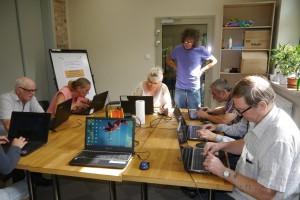 Grupa osób siedzi wokół stołów i pisze na laptopach, instruktor stoi i przygląda się pracy