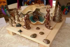 Szopka wykonana z ceramiki. Żłóbek zamieszczony w muszli, obok święta rodzina, koniki morskie oraz muszelki