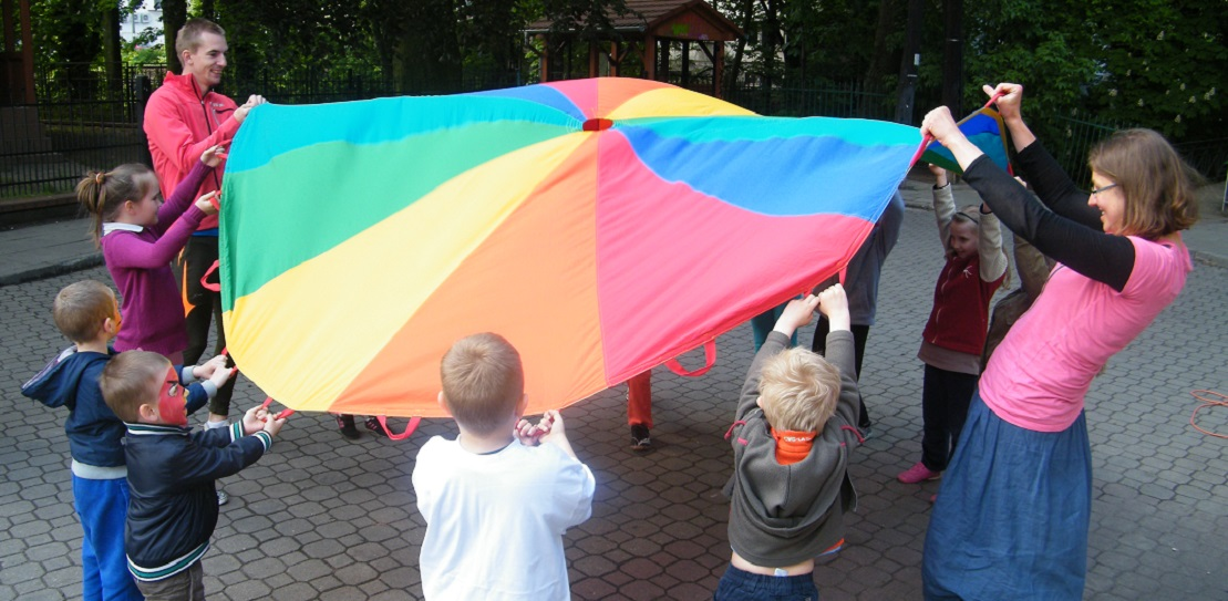 Grupa dzieci stojąc w kole trzyma kolorową chustę za rogi i podrzuca nią do góry
